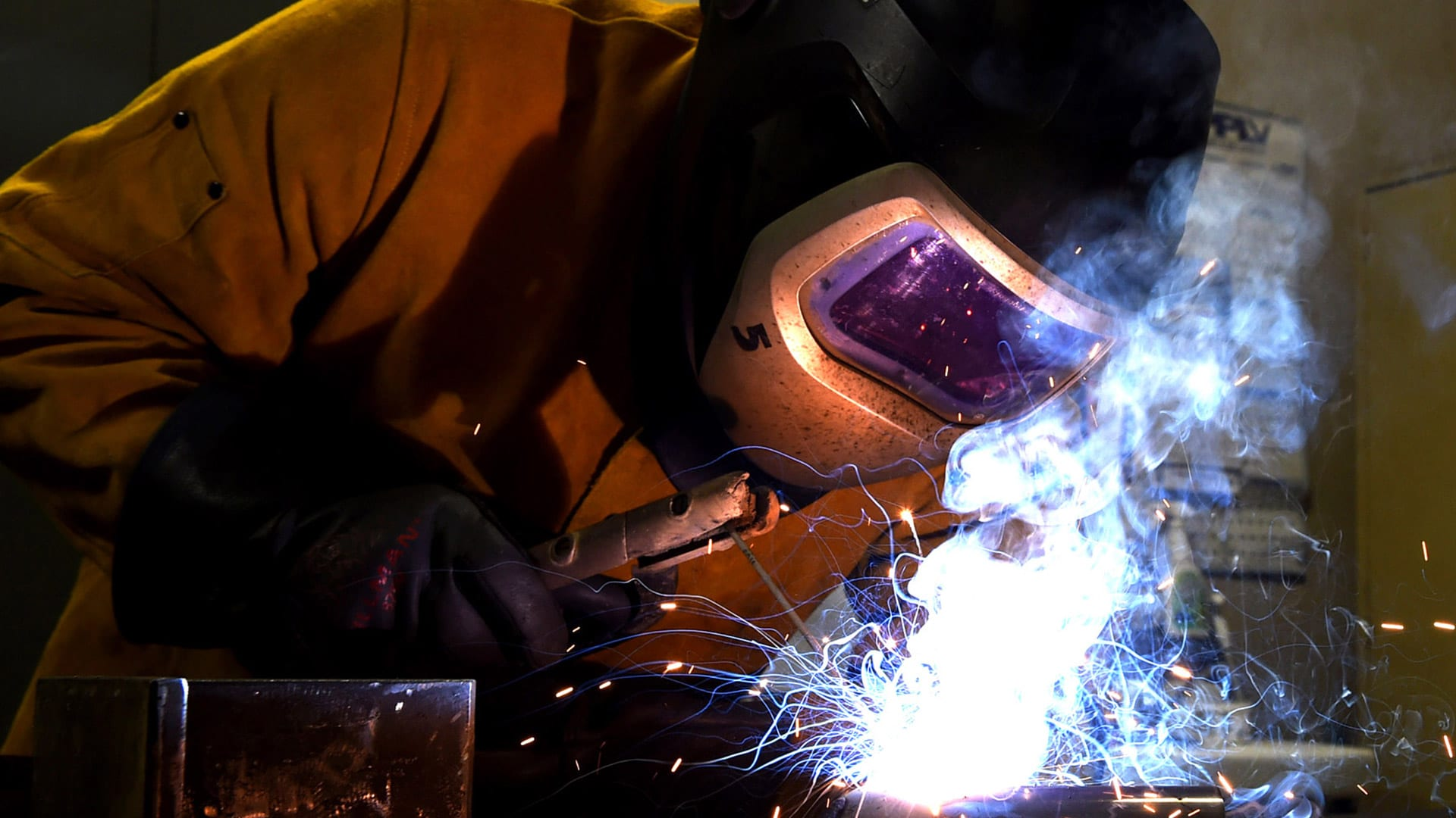 man welding a compressor
